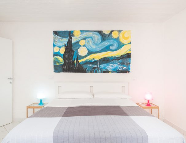 A queen bed with grey bed cover, two nightstands and a Van Gogh murales on the wall