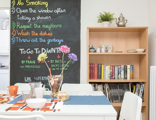 A table prepared with mugs for breakfast and a blackboard on the wall with the house's rules