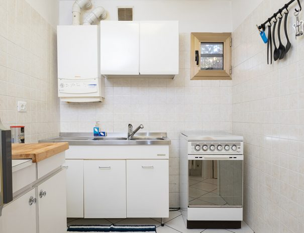 A white kitchen with the oven and little window