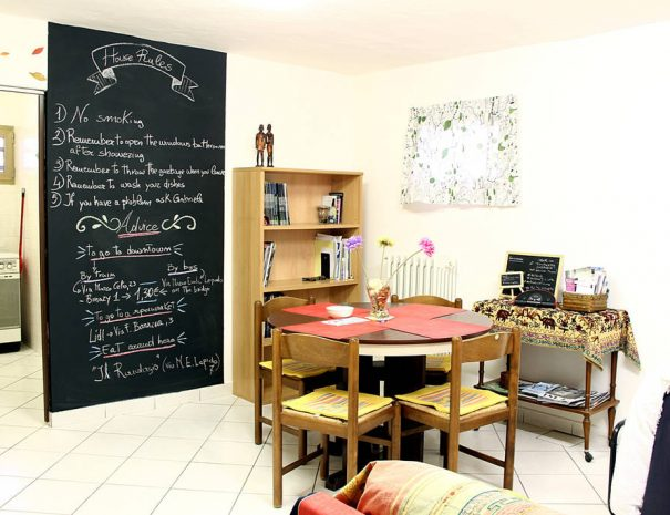 A living room with a dining table and blackboard rules on the wall