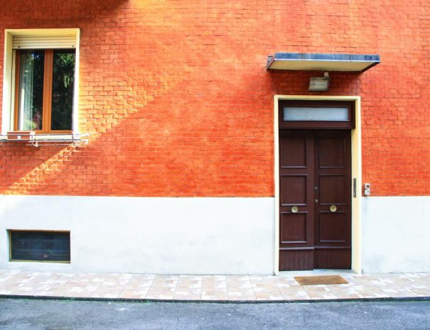 The front of the building with red doorway and red bricks