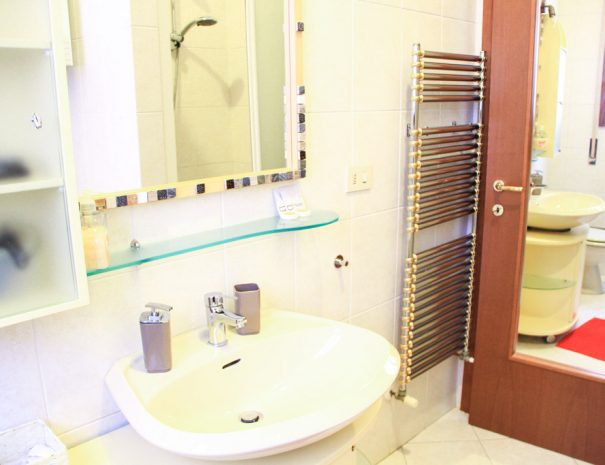 A bathroom with silk, mirror and another mirror on the door