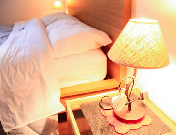 A lighted lamp on the beside table in the bedroom