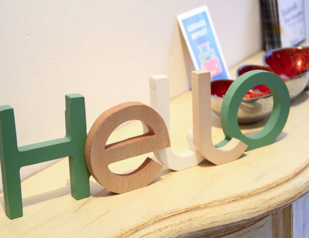 A wood write says hello with white, yellow and green color