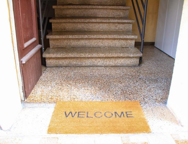 The entrance of the building with a doormat says welcome